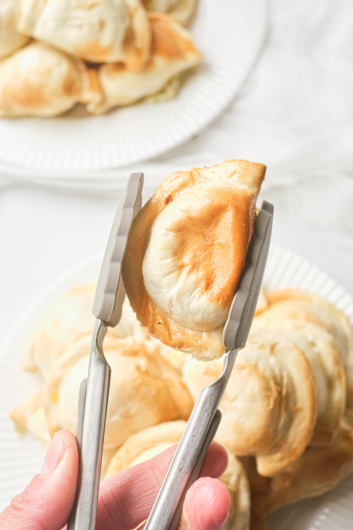 one air fryer pierogie being picked up with tongs