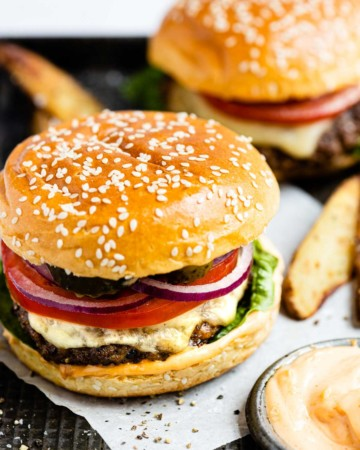 the completed venison burgers recipe served with potato wedges and dipping sauce