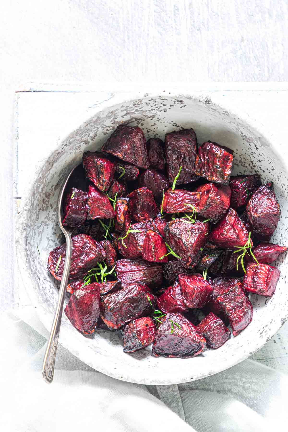 the finished air fryer beets served in a ceramic bowl with silver spoon