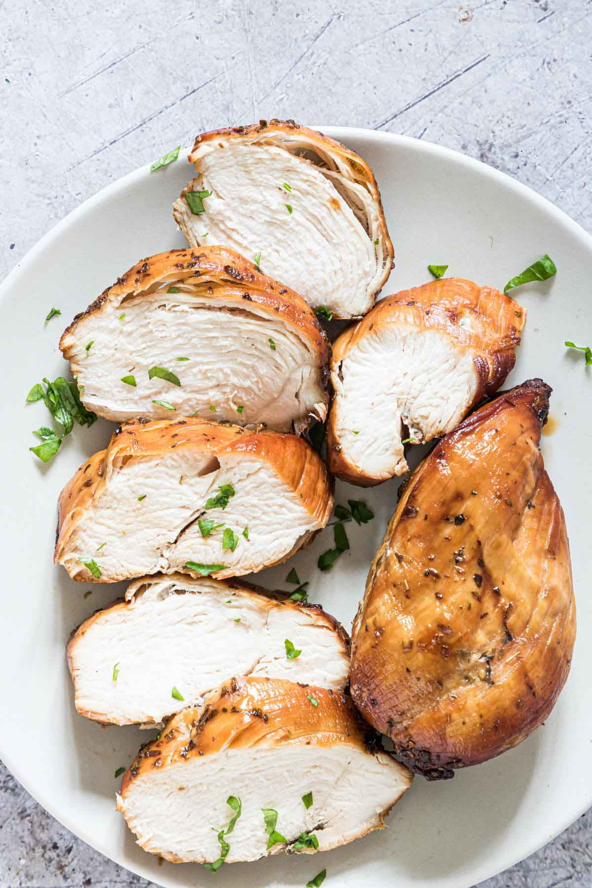 top down view of the cooked air fryer frozen chicken breast sliced and served on a white plate