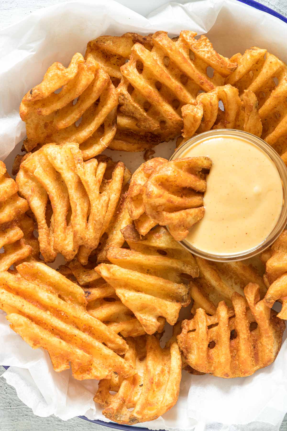 close up view o a serving of waffle fries and a dish of chick fil a sauce