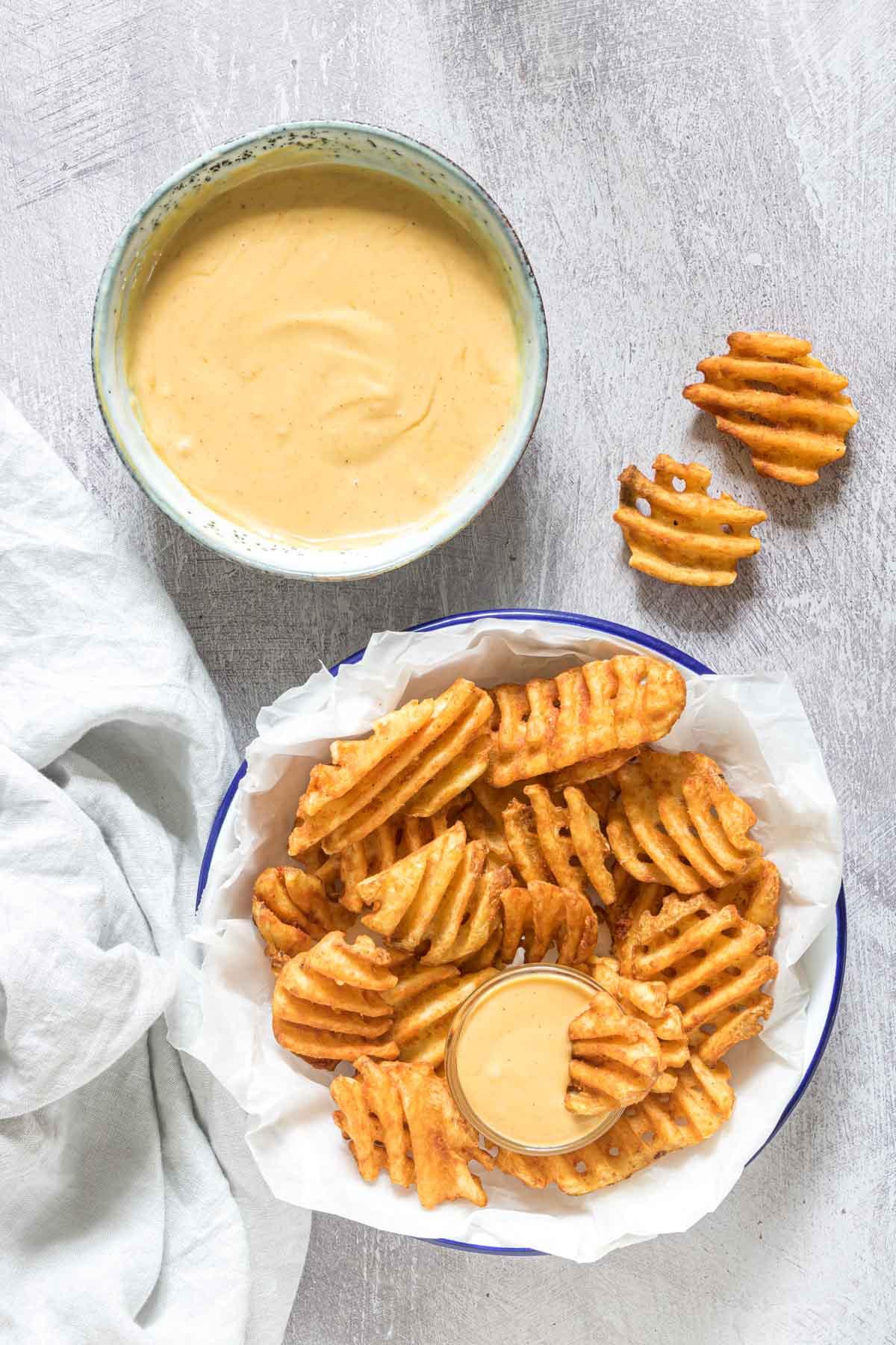 a plate of waffles fries served alongside a bowl of copycat chick fil a sauce