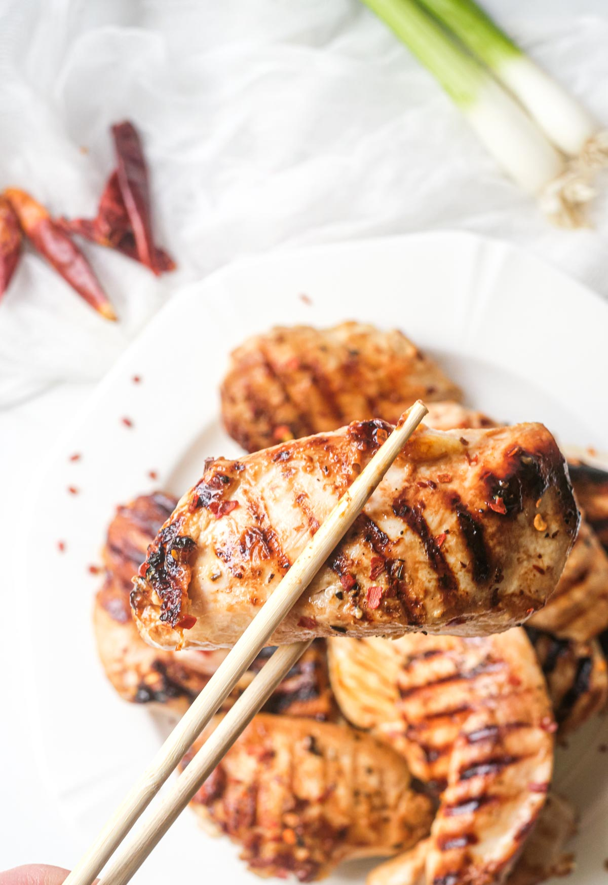 one of the Asian grilled chicken tenders being picked up with chopsticks