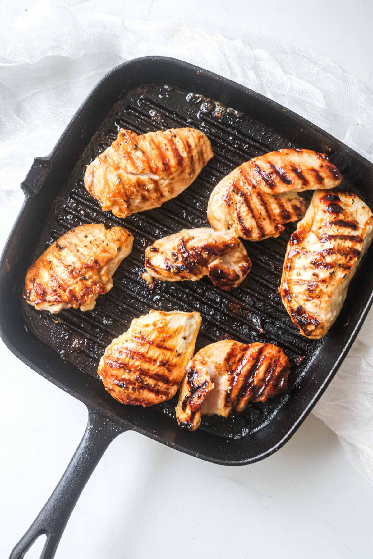the chicken tenders inside being cooked in a grill pan