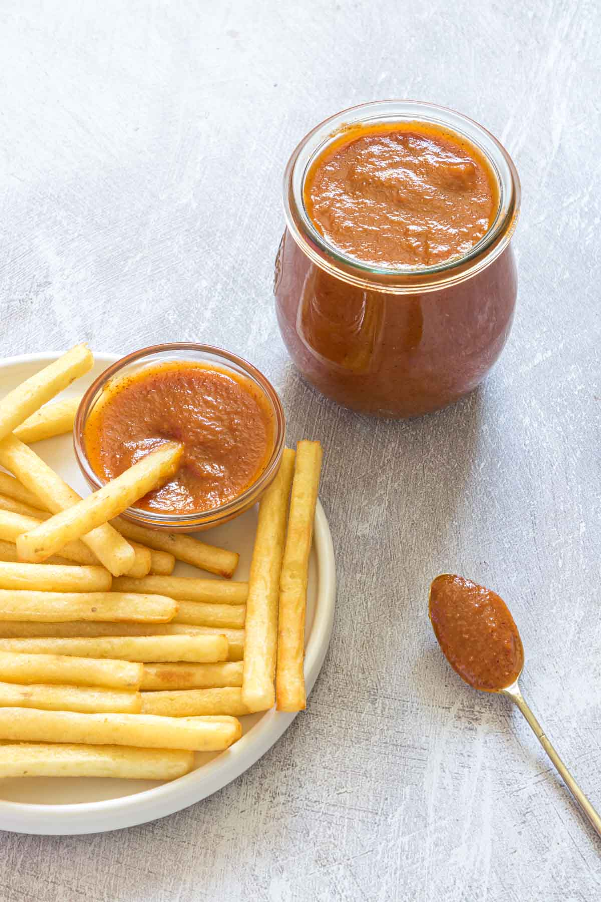some homemade tomato ketchup served with some fries on a plate, with a spoon of ketchup on the side