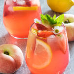 close up up of fresh peach lemonade on a table with fruit