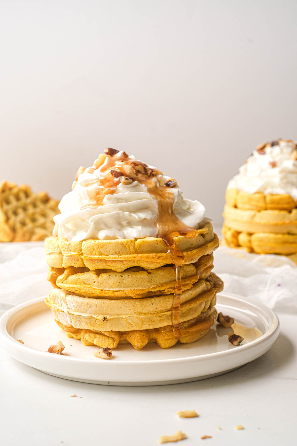 a stack of pumpkin waffles topped with whipped cream, syrup and nuts