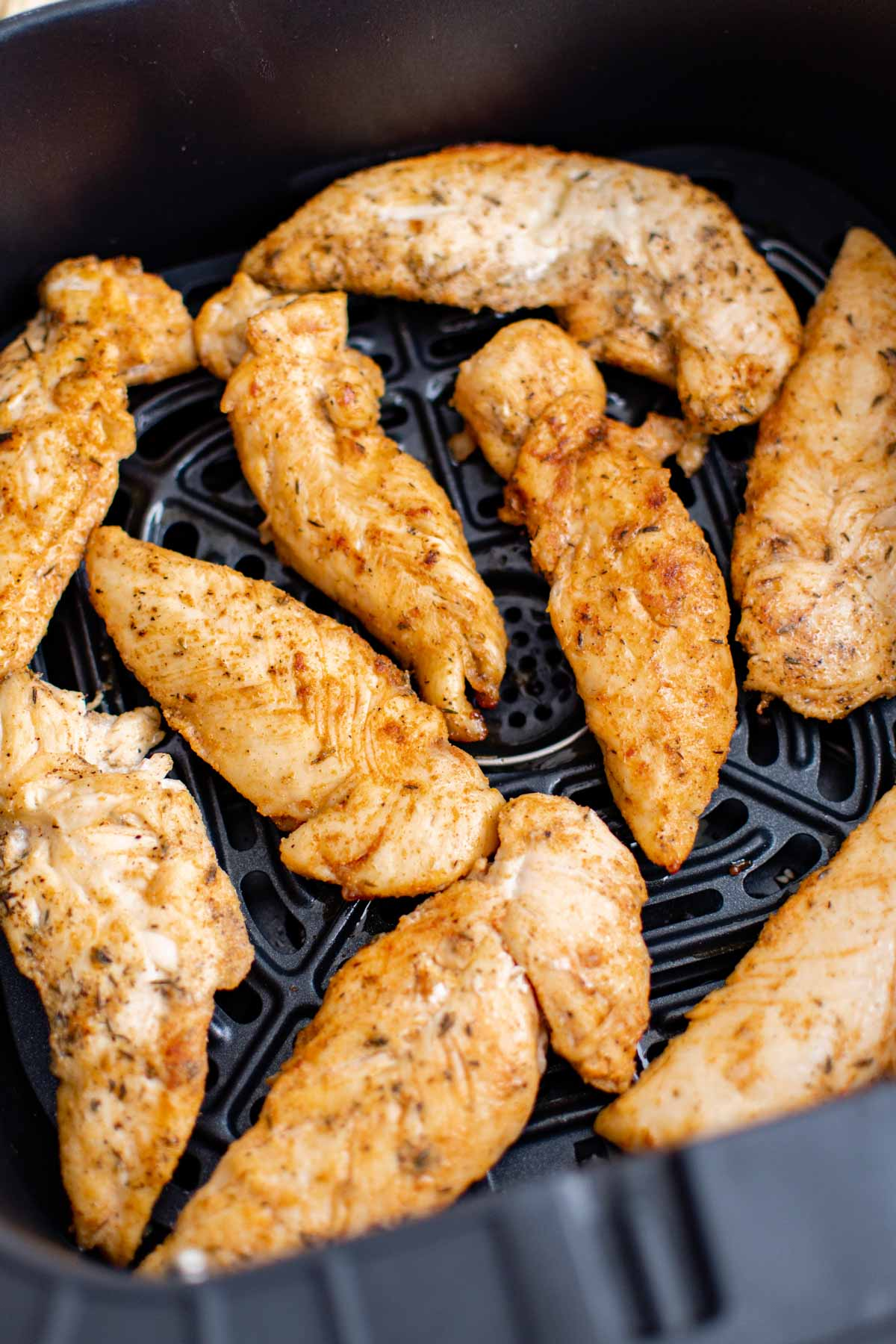 close up view of the cooked chicken tenders inside the air fryer basket