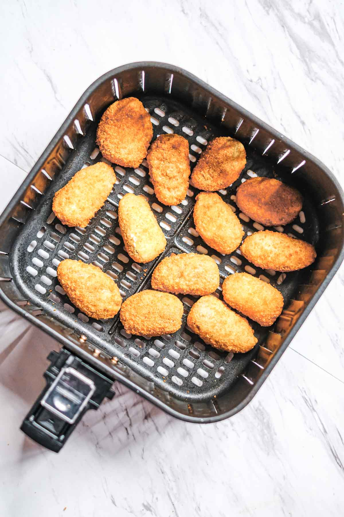 top down view of the frozen jalapeno poppers in air fryer basket