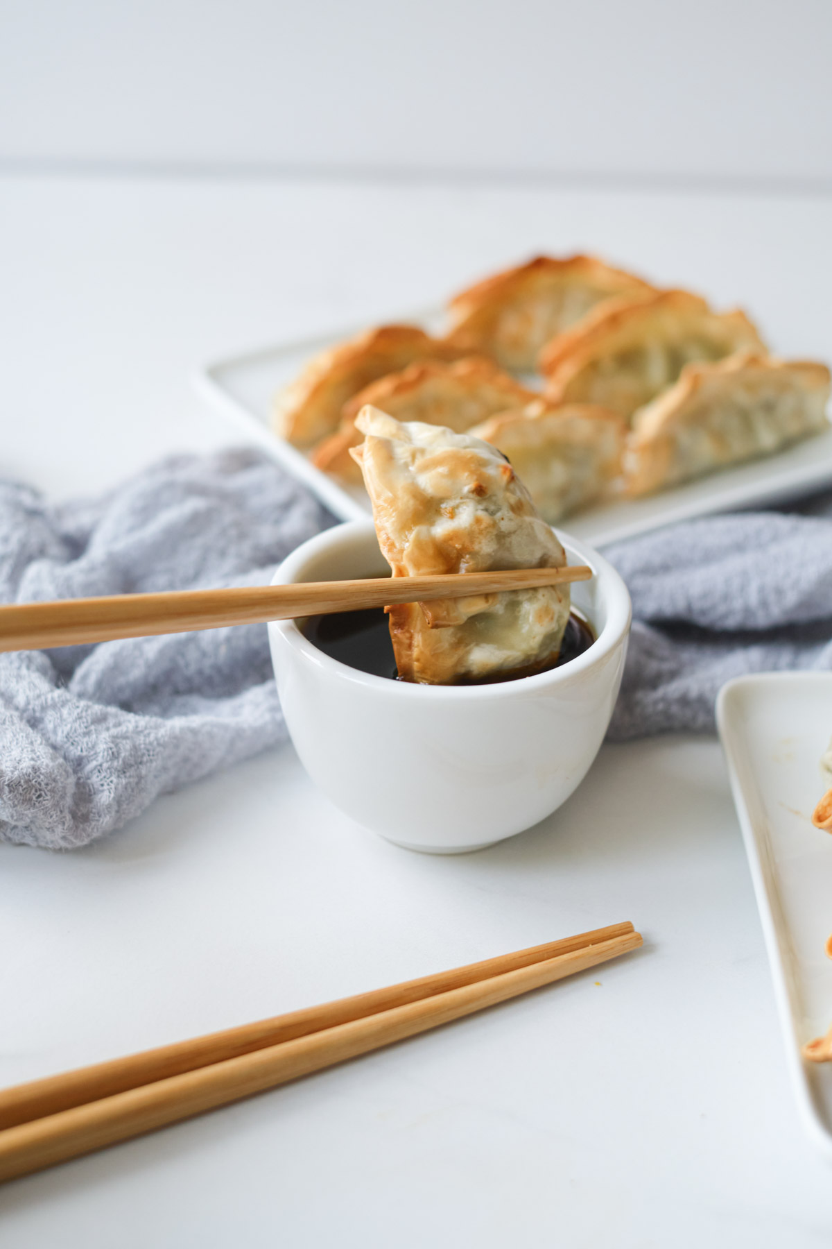 one air fryer frozen potsticker being dunked in dipping sauce