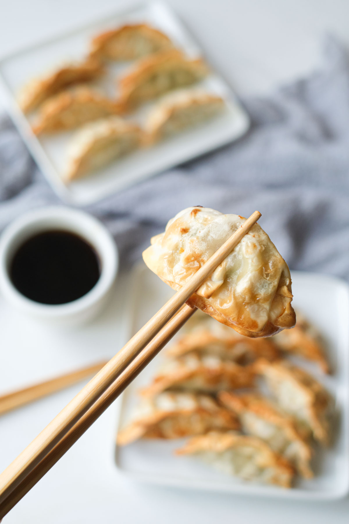 one of the completed air fryer frozen potstickers held by chopsticks