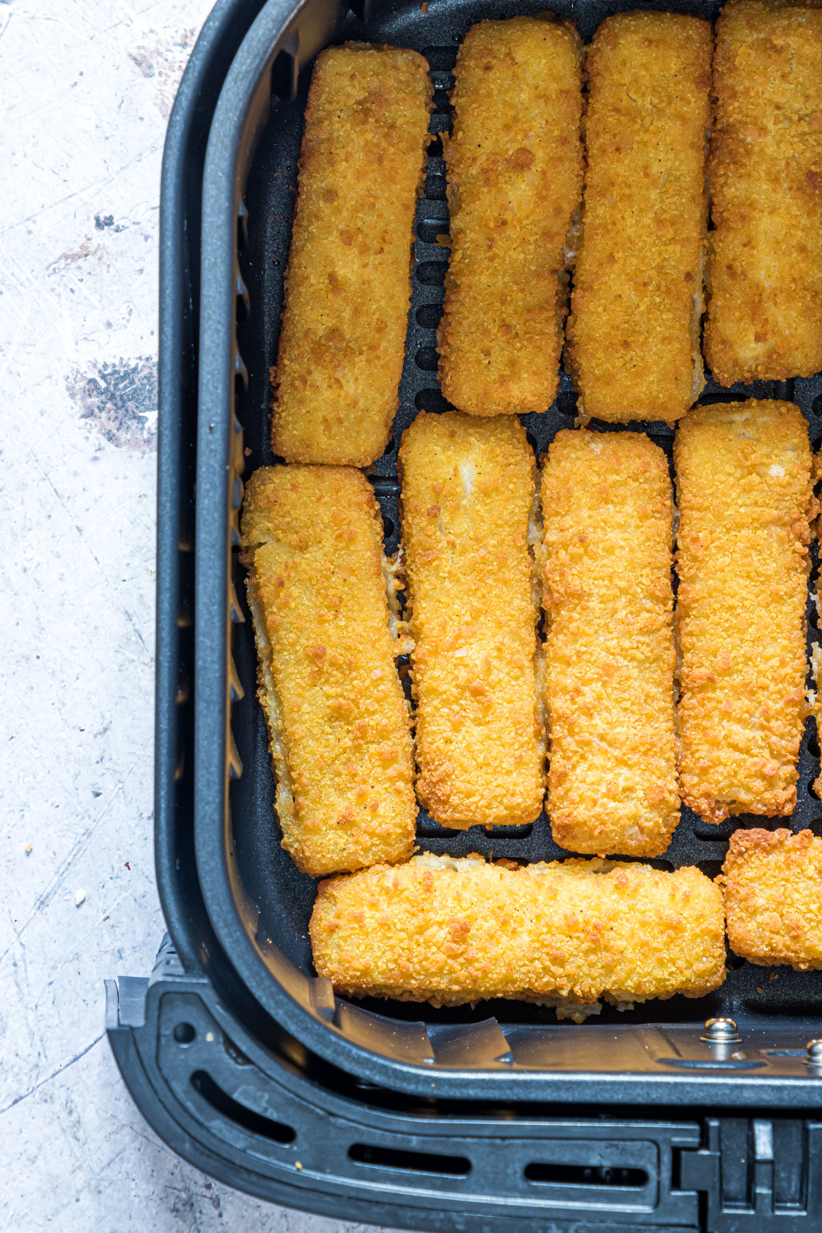 close up view of the cooked frozen fish sticks in air fryer basket