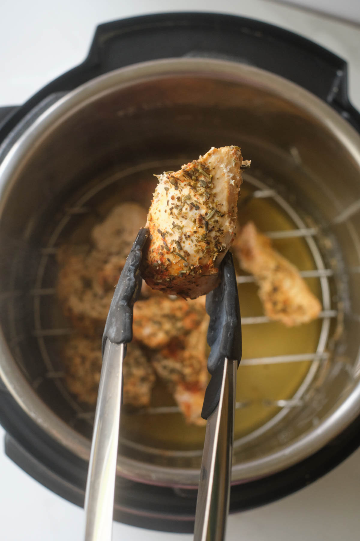 top down view of one of the instant pot chicken tenders being removed with tongs