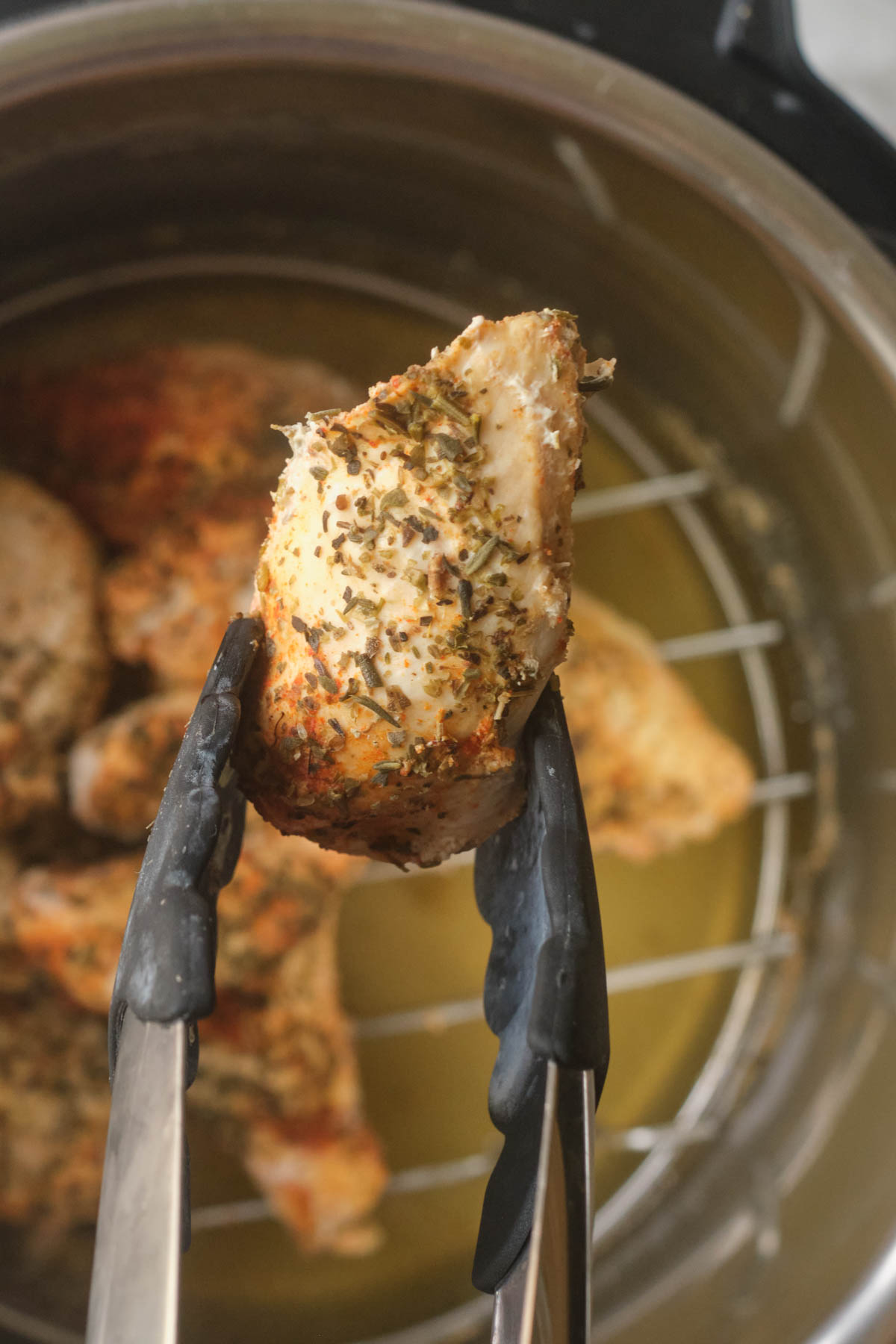 one of the finished instant pot chicken tenders being removed from the instant pot with tongs