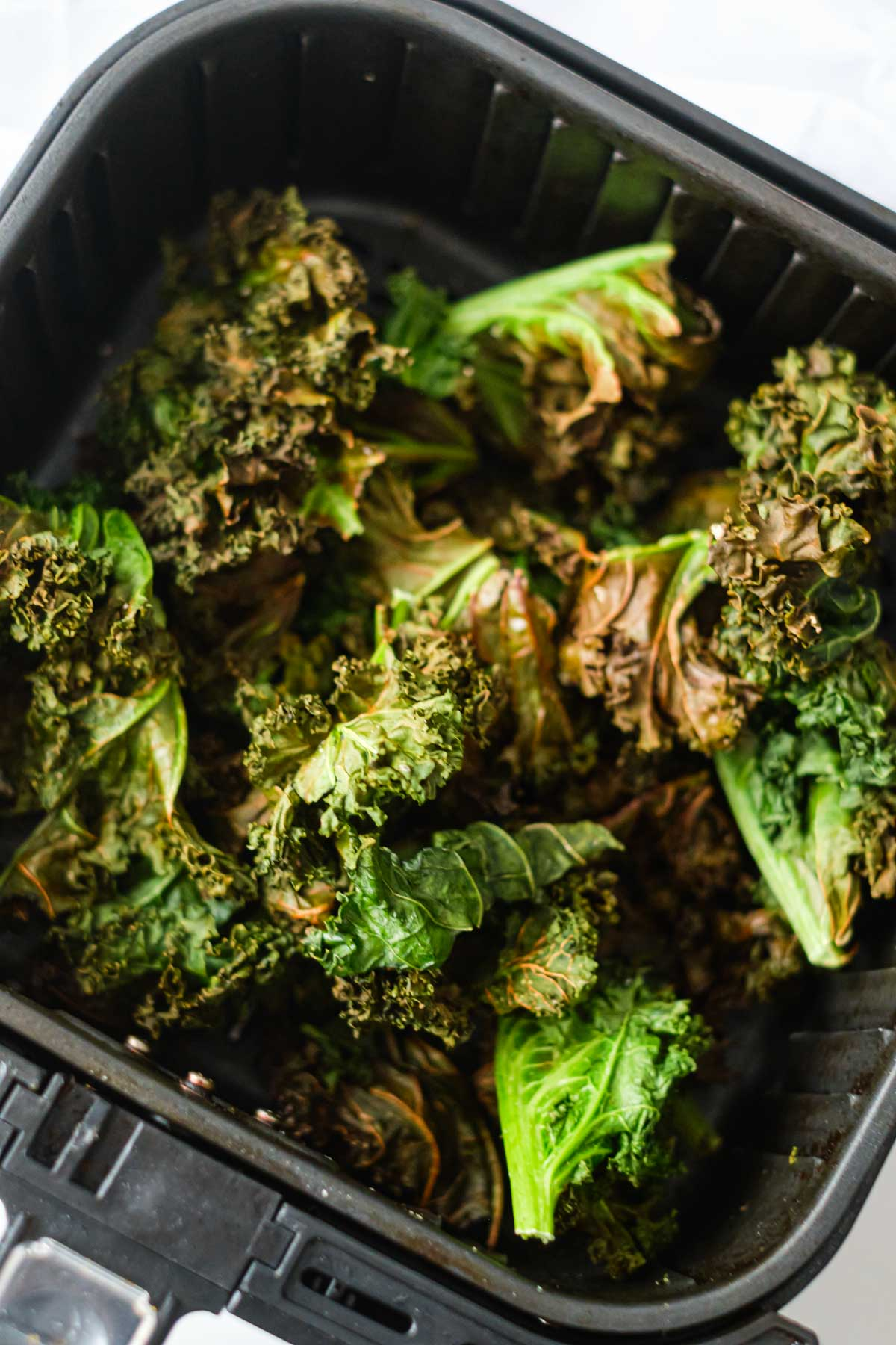 top down view of the cooked air fryer kale chips inside the air fryer basket