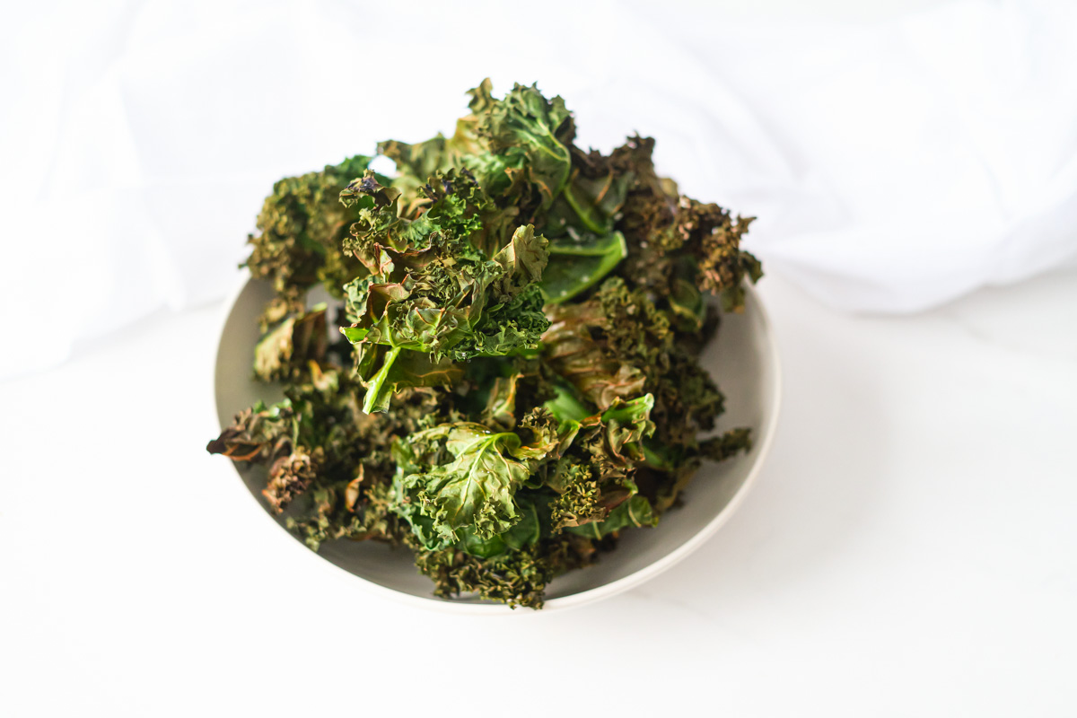 a white bowl filled with air fryer kale chips