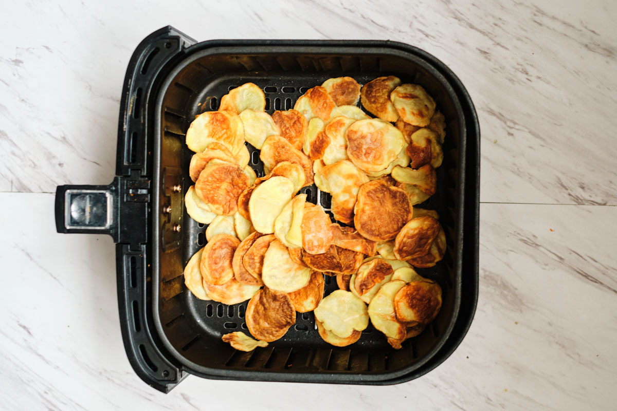 top down view of the completed air fryer potato chips inside the air fryer basket