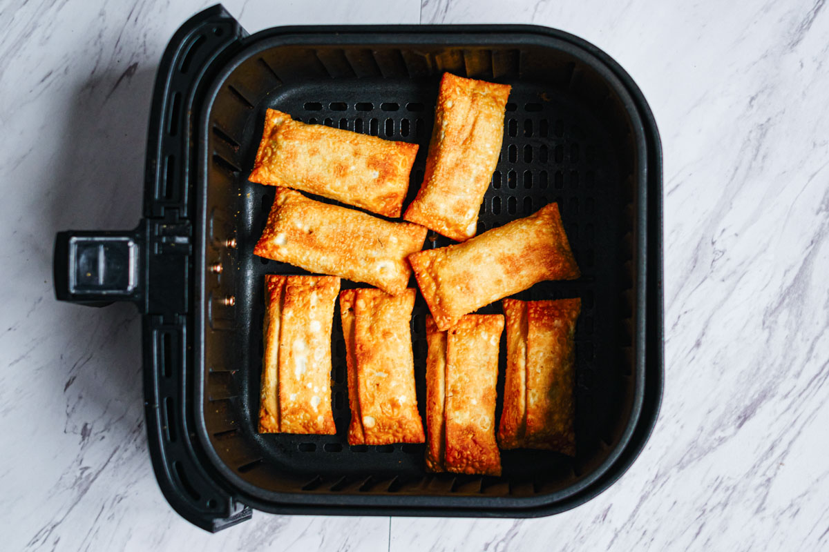 top down view of the cooked frozen egg rolls in air fryer basket