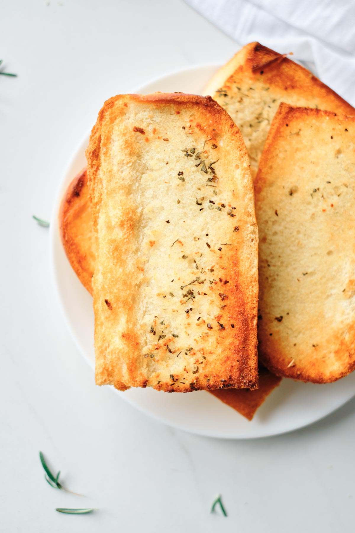 the finished version of frozen garlic bread in air fryer served on a whiter plate