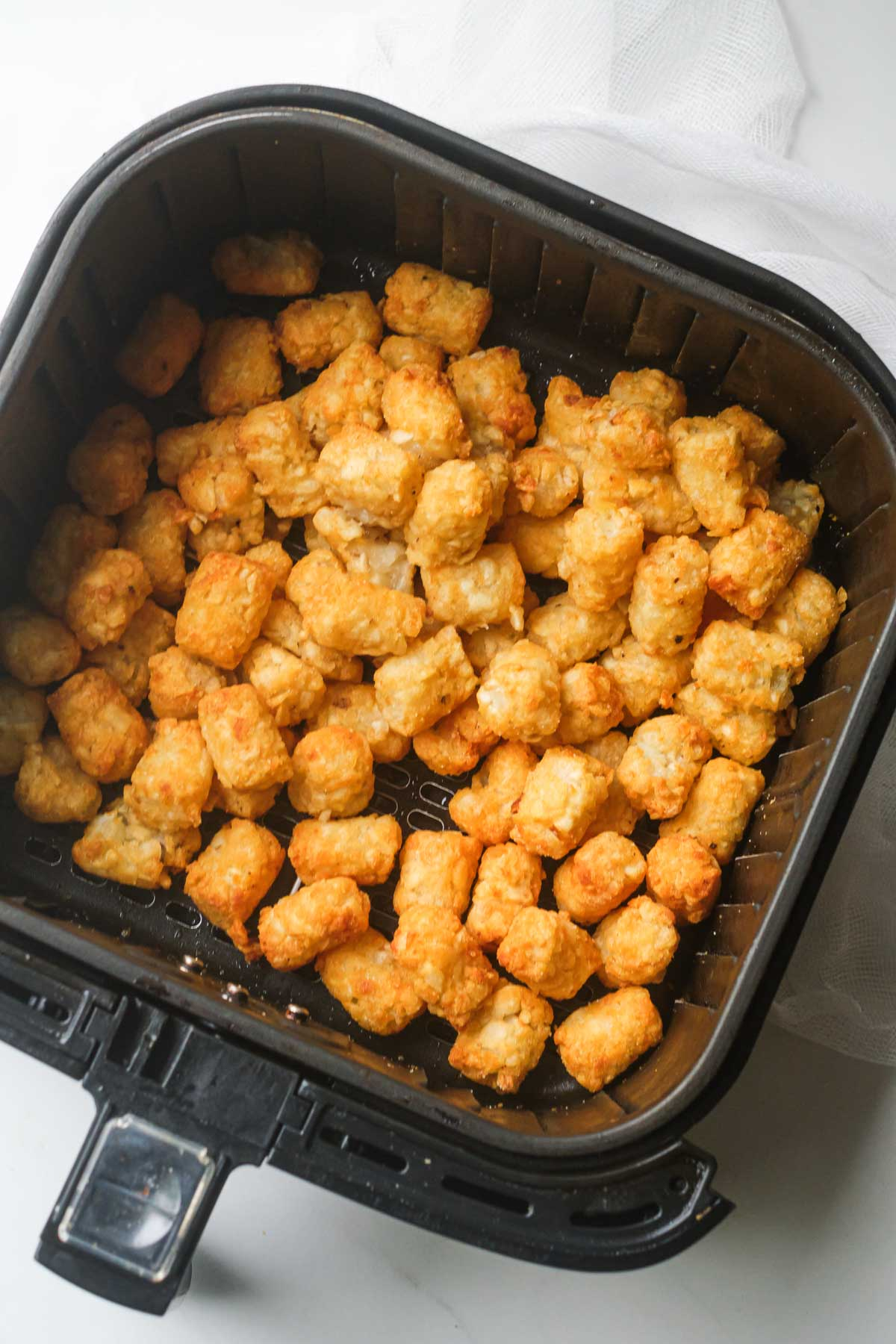 top down view of the cooked air fryer frozen tater tots inside the air fryer basket