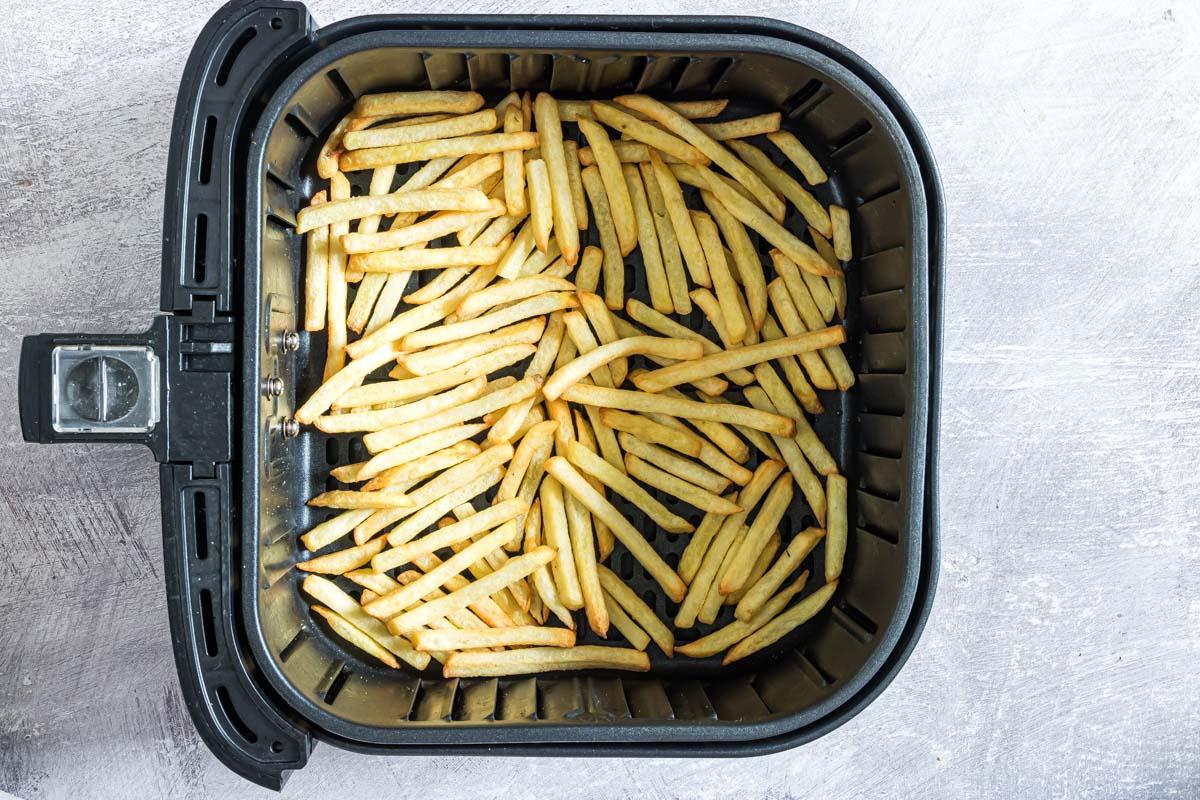 top down view of fries reheating in air fryer basket