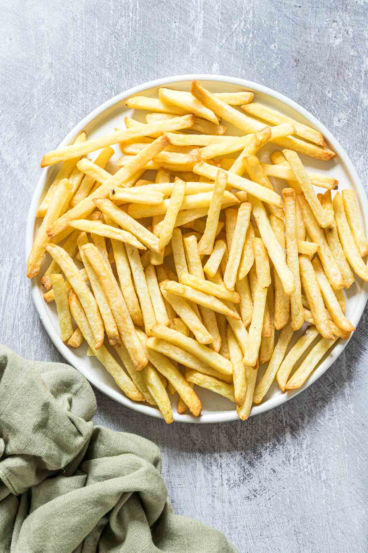 a serving of air fryer reheat fries on a white plate with green cloth napkin