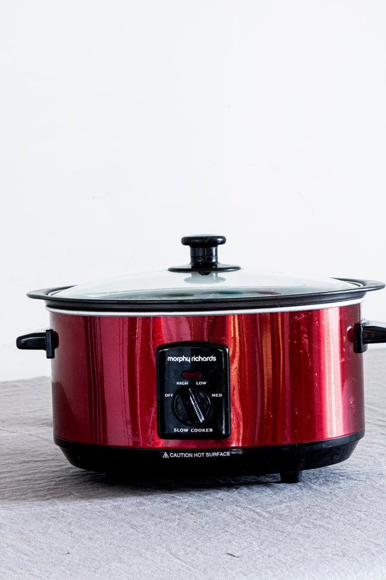 a red slow cooker on a countertop