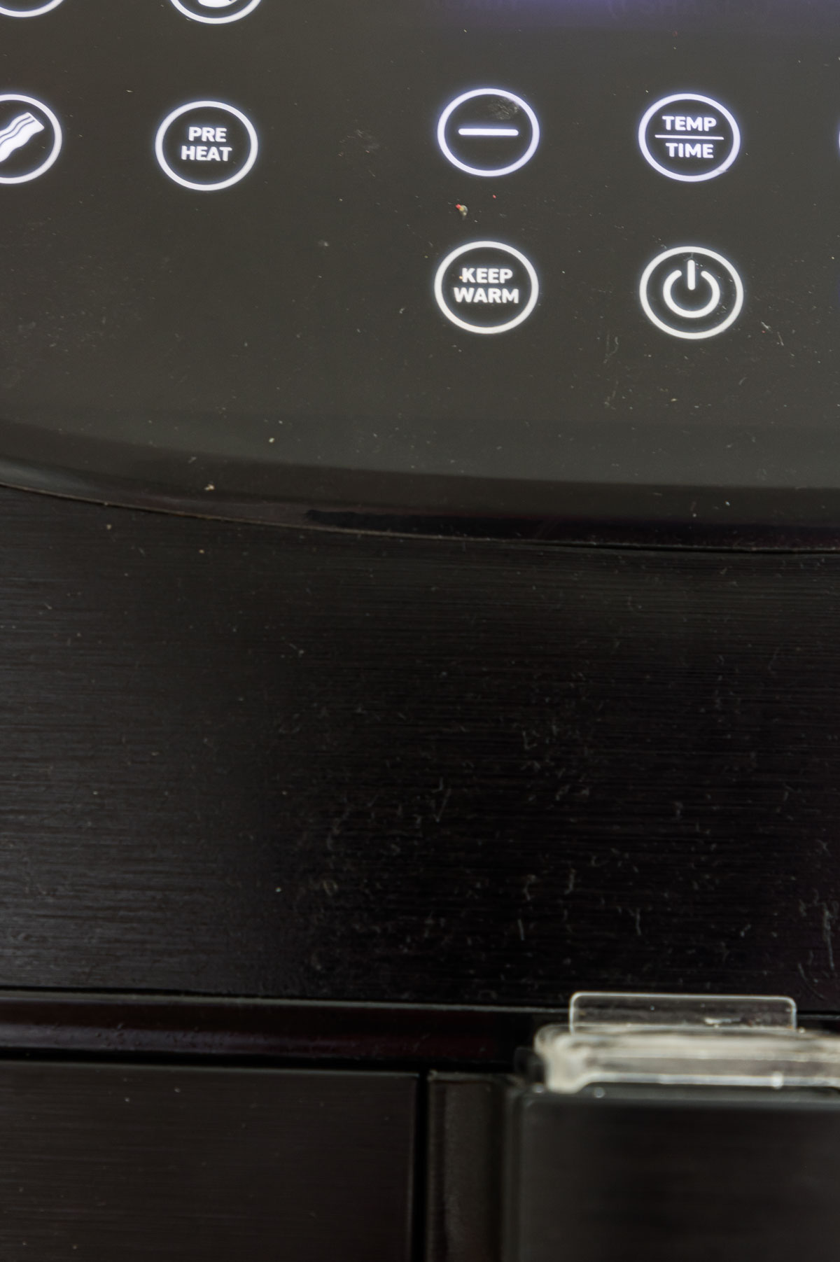 close up view of the preheat button on the panel of the air fryer