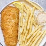 a serving of fish that has been reheated in air fryer along with french fried and tartar sauce
