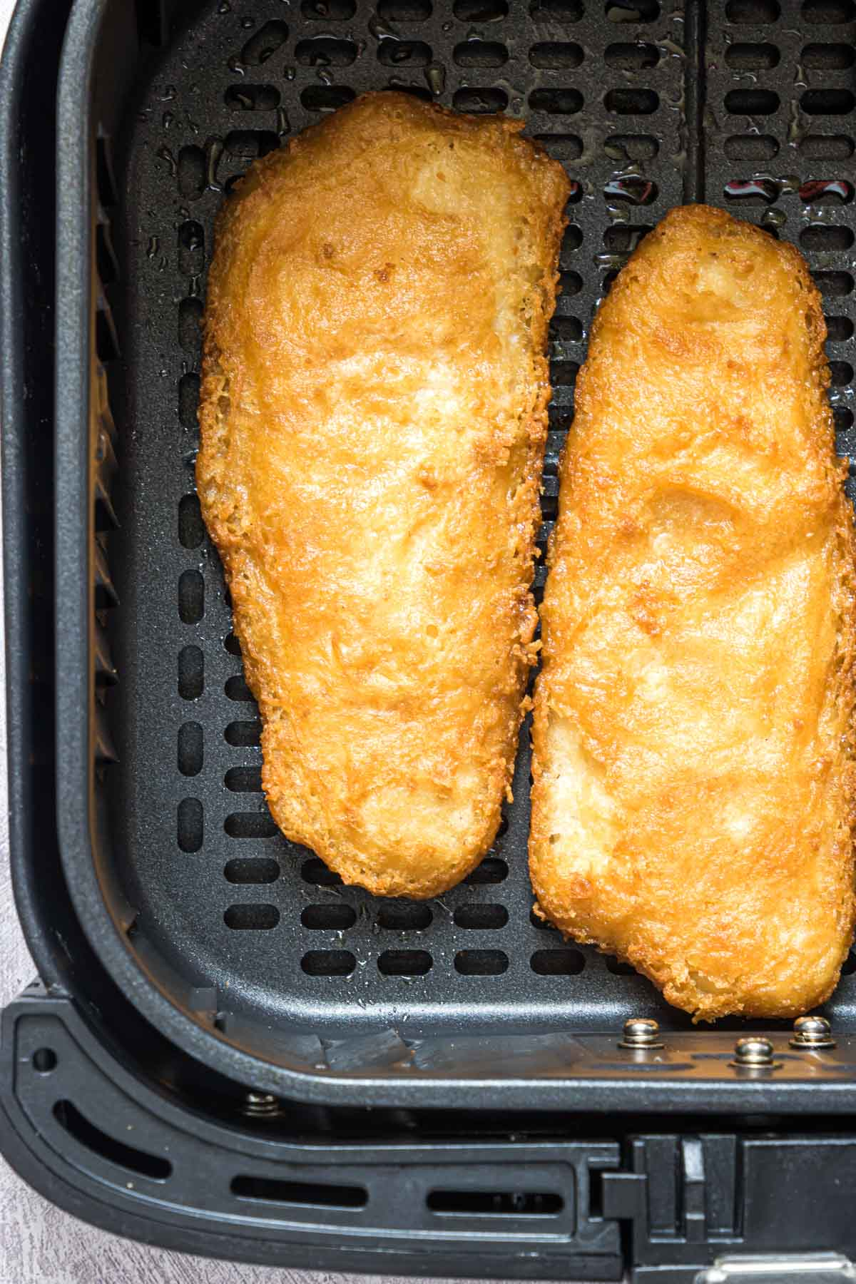 close up view of reheat fried fish inside the air fryer basket