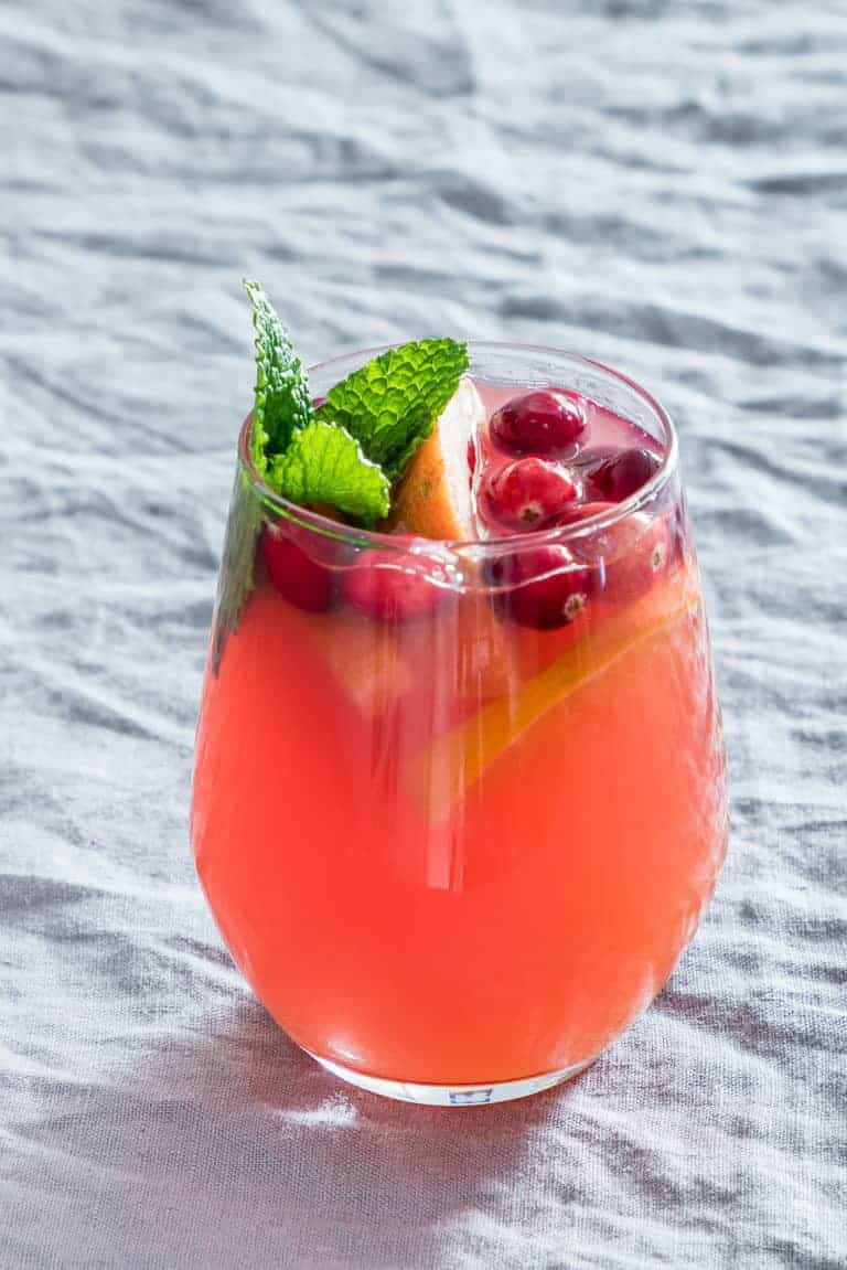 a glass of festive punch garnished with fruit and mint