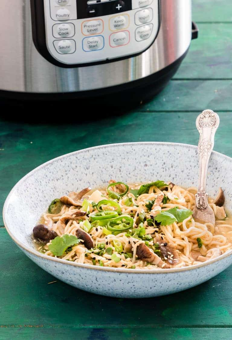 A bowl of Instant Pot Ramen served with a silver spoon and sitting in front o f the Instant Pot