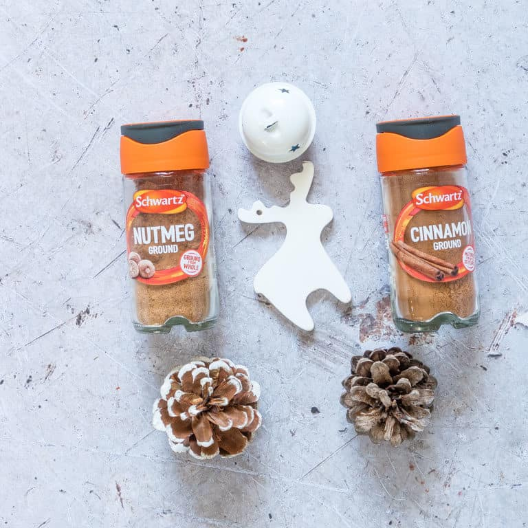 Schwartz nutmeg and cinnamon jars next to White Christmas ornaments and two pinecones