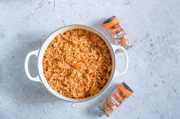 Cinnamon Spiced Jollof Rice in a white pot set next to a jar of cinnamon and a jar of nutmeg