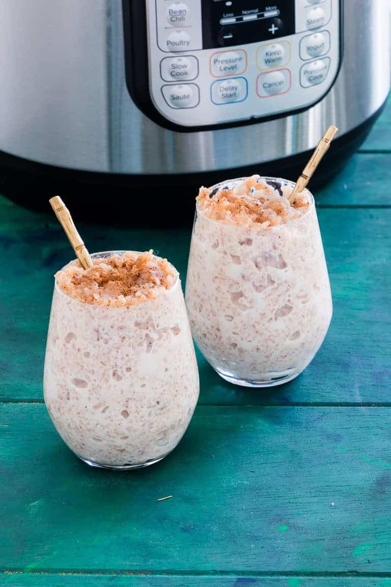 Two servings of Instant Pot Arroz Con Leche with gold spoons set in front of the Instant Pot