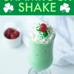 A GREEN SHAKE WITH WHIPPED CREAM AND CHERRY IN A GLASS