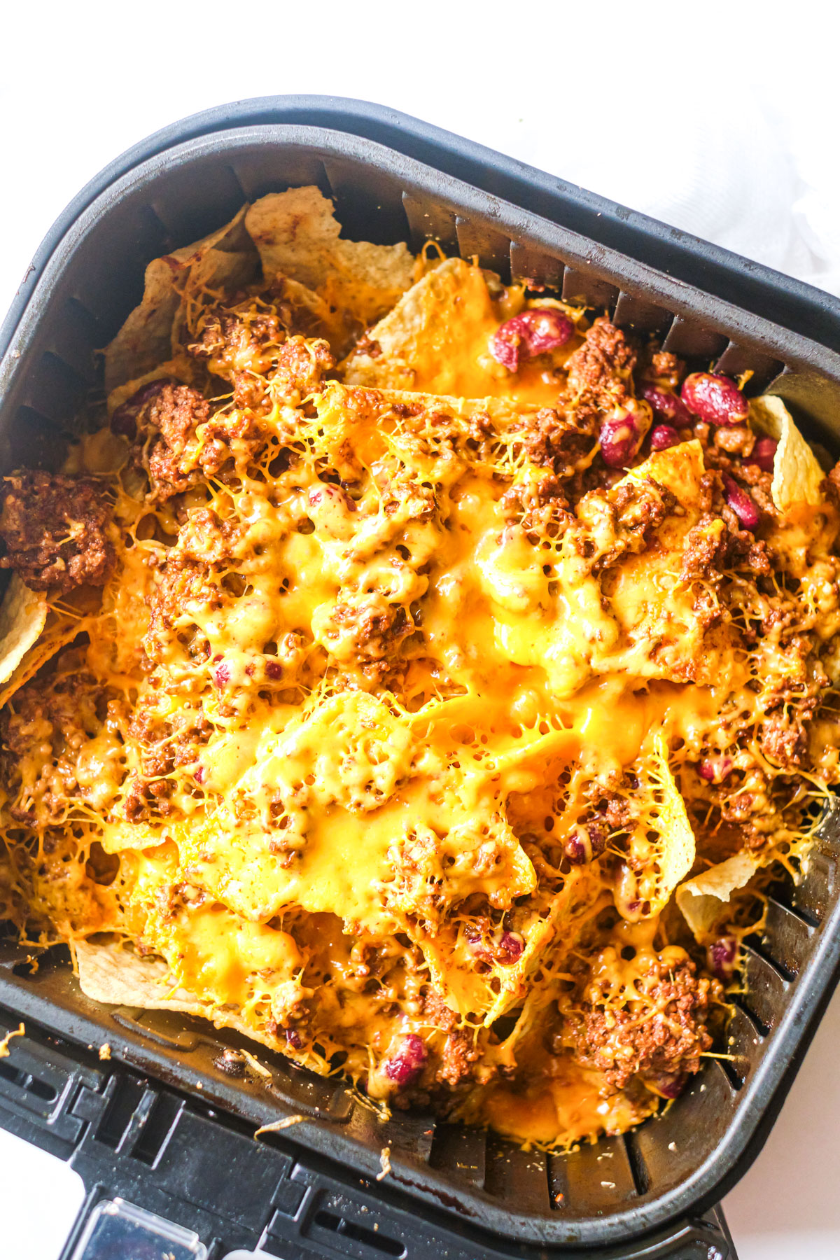 an air fryer basket filled with chili nachos