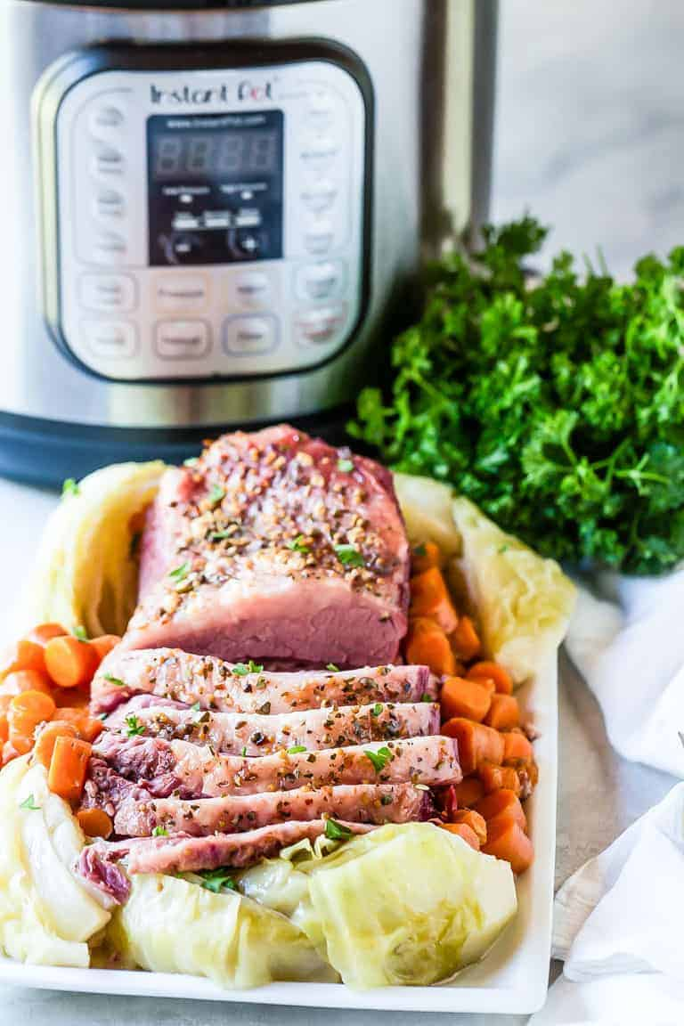 Instant Pot Corned Beef and Cabbage ready to serve on a white platter with parsley and carrots