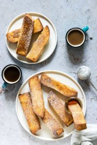 two plates of Air Fryer French Toast Sticks served with syrup and powdered sugar