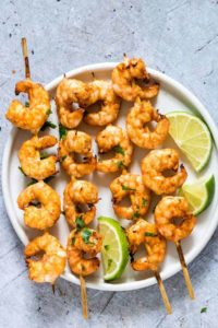 Air Fryer Shrimp Skewers on a while plate an garnished with chopped cilantro and lime wedges
