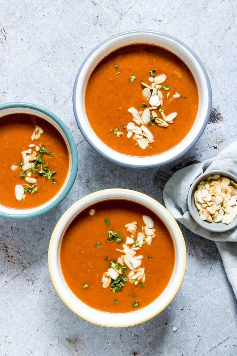 three bowls of instant pot tomato soup topped with sliced almond and chopped herbs