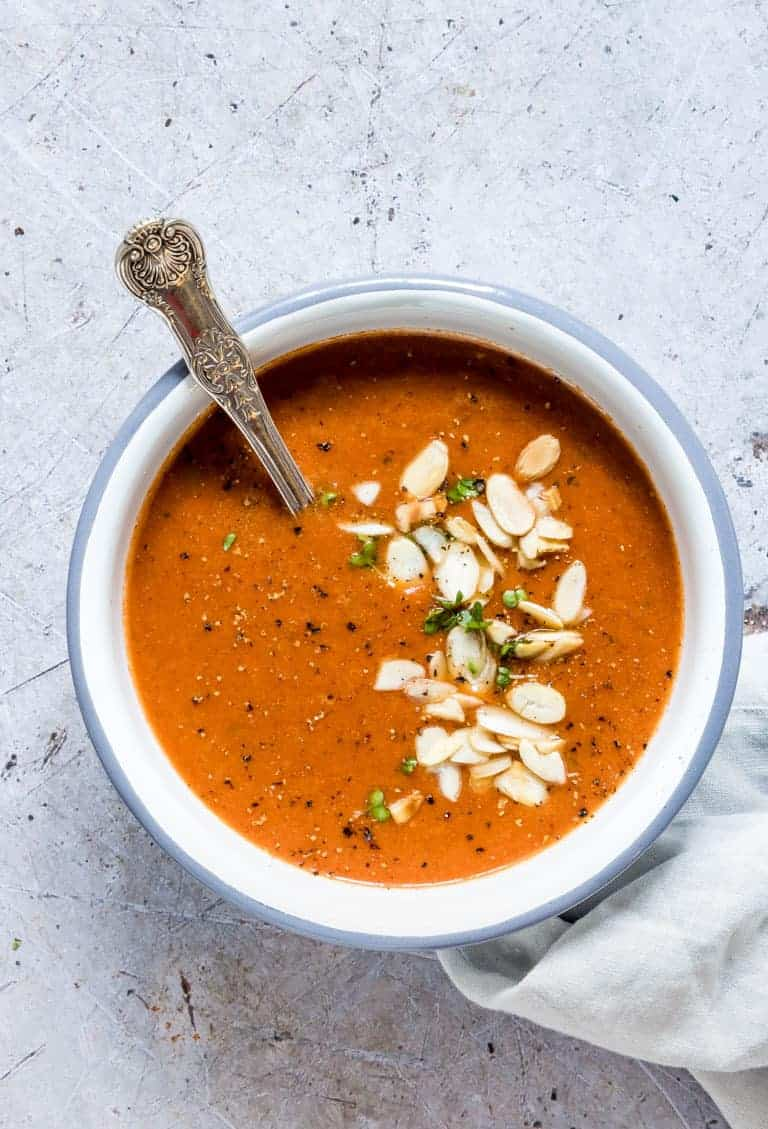 Instant Pot Tomato Soup servved in a ceramic bowl and topped with sliced almonds and chopped fresh herbs