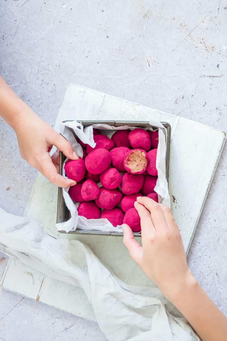 two hands reaching into a square contained filled with beetroot covered chocolate truffles