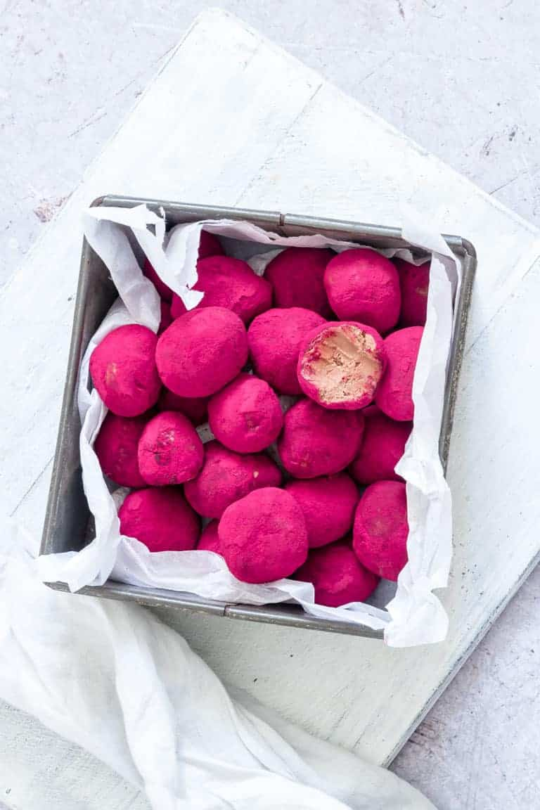the completed beetroot covered chocolate truffles in a square container with one bite taken out of a truffle set on top