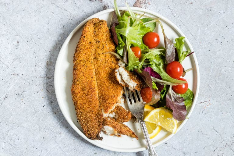 close up view of a serving of air fryer fish and a green salad on a white dinnert plate