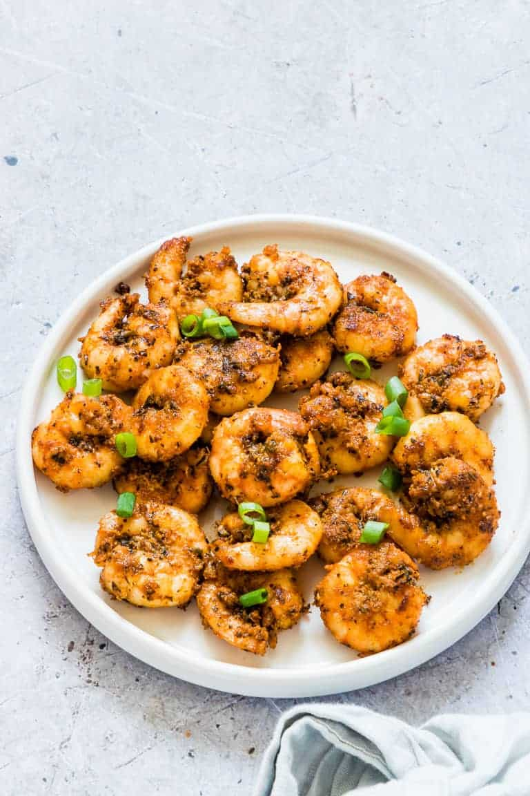 healthy cajun shrimp recipe garnished with green onion and served on a white plate
