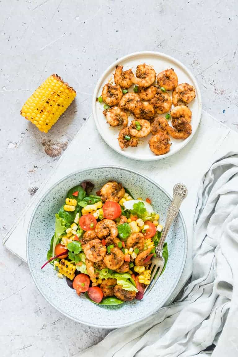 A serving of Cajun Shrimp Salad Recipe in a blue ceramic bowl next to a piece of grilled corn and a plate of cooked Cajun Shrimp