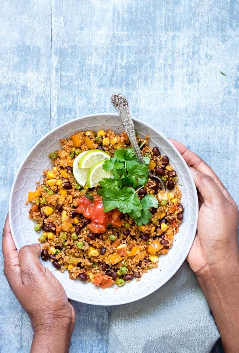 two hands holding a bowl of Dump and Start Instant Pot Mexican Quinoa