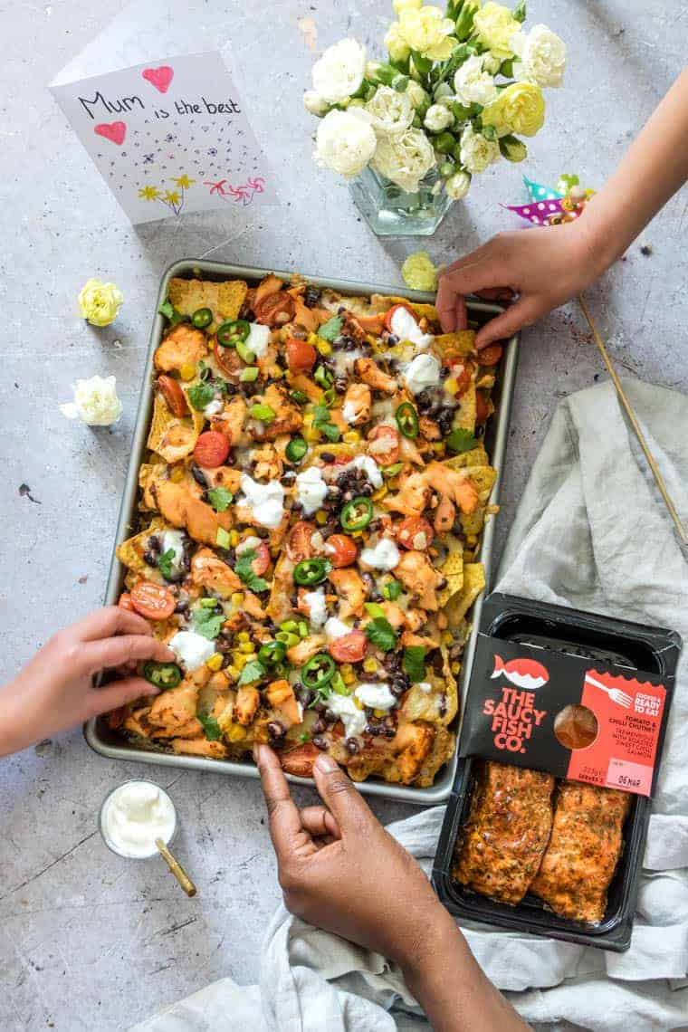 kids hands reaching into a sheet pan filled with salmon black bean nachos placed next to a vase of flowers and homemade mother's day card