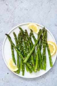 air fryer asparagus served on a white plate with fresh lemon wedges